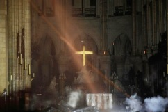 Smoke rises around the alter in front of the cross inside the Notre-Dame Cathedral as the fire continues to burn on April 16, 2019 in the French capital Paris. - A huge fire swept through the roof of the famed Notre-Dame Cathedral in central Paris on April 15, 2019, sending flames and huge clouds of grey smoke billowing into the sky. The flames and smoke plumed from the spire and roof of the gothic cathedral, visited by millions of people a year. A spokesman for the cathedral told AFP that the wooden structure supporting the roof was being gutted by the blaze. (Photo by PHILIPPE WOJAZER / POOL / AFP)