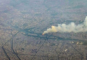 "This handout grab of a video taken from a plane on April 15, 2019 shows smoke and flames rising during a fire at the landmark Notre-Dame Cathedral in central Paris. - Pledges from French billionaires, businesses and the public sector to help rebuild Notre-Dame cathedral have reached nearly 700 million euros (790 million dollars) amid an outpouring of public support for one of Europe's most iconic monuments. (Photo by HO / Maxime BRUNET/ELASTIQUEPROD / AFP) / RESTRICTED TO EDITORIAL USE - MANDATORY CREDIT ""AFP PHOTO /MAXIME BRUNET/ELASTIQUEPROD"" - NO MARKETING - NO ADVERTISING CAMPAIGNS - DISTRIBUTED AS A SERVICE TO CLIENTS - NO ARCHIVE - ALTERNATIVE CROP"