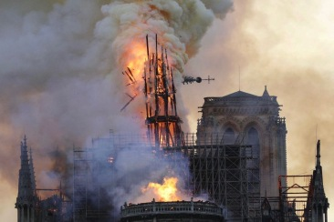 The steeple and spire collapses as smoke and flames engulf the Notre-Dame Cathedral in Paris on April 15, 2019. - A huge fire swept through the roof of the famed Notre-Dame Cathedral in central Paris on April 15, 2019, sending flames and huge clouds of grey smoke billowing into the sky. The flames and smoke plumed from the spire and roof of the gothic cathedral, visited by millions of people a year. A spokesman for the cathedral told AFP that the wooden structure supporting the roof was being gutted by the blaze. (Photo by Geoffroy VAN DER HASSELT / AFP)