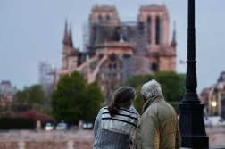 "A couple looks on as firefighters work to extinguish a fire at Notre-Dame Cathedral in Paris early on April 16, 2019. - A huge fire that devastated Notre-Dame Cathedral is ""under control"", the Paris fire brigade said early on April 16 after firefighters spent hours battling the flames. (Photo by Zakaria ABDELKAFI / AFP)"